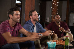 Three male friends playing video games and drinking at home Royalty Free Stock Image