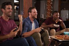 Three male friends playing video games and eating at home Stock Image