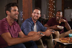 Three male friends playing video games looking at each other royalty free stock photo