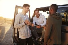 Three male friends on a road trip using a tablet computer royalty free stock image