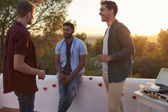 Three male friends talk at a party on a rooftop at sunset Royalty Free Stock Photos