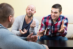 Three male friends talking at home Stock Images