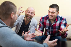 Three male friends talking at home Stock Photos