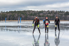 Three male ice skaters on wet watery and frozen lake. Royalty Free Stock Image