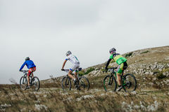Three male riders cyclists mountenbike ride a mountain trail Royalty Free Stock Photo