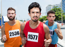 Three male runners during a marathon race in city Royalty Free Stock Image