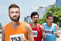 Three male runners during a race in city Royalty Free Stock Image