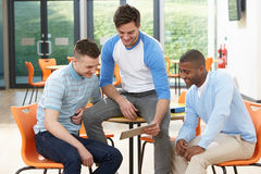 Three Male Students Looking At Digital Tablet In Classroom. Laughing Royalty Free Stock Photography