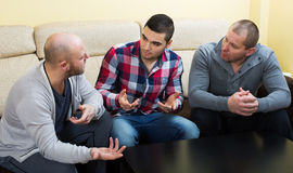 Three males  at home. Three males having a serious conversation at home Stock Images