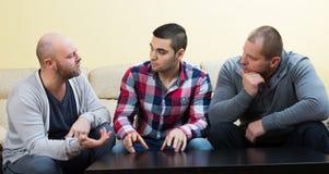 Three males  at home. Three males having a serious conversation at living room Royalty Free Stock Photo