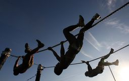 Three Man Climbing on Rope Under the Sunset Stock Images