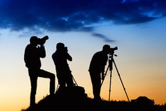 Three man silhouettes photographing the sky. On sunset Stock Photo