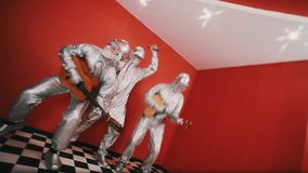 Three man in silver hazard suits playing music instruments and dancing. Three man in silver hazard suits and hard hats, goggles and white face paint robot stock footage