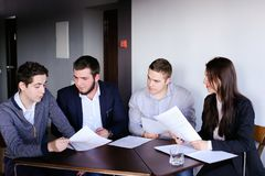Four colleagues of man and woman gather for meeting at office of. Three managers who are held discuss agenda and are waiting for start of business meeting with royalty free stock image