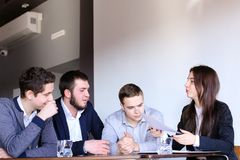 Four colleagues of man and woman gather for meeting at office of Royalty Free Stock Photography