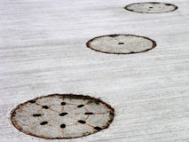 Three manholes 2. Three flushcovers in concrete pavement Royalty Free Stock Images
