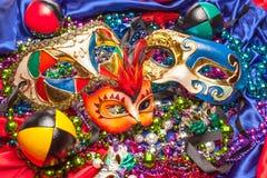 Three Mardi Gras Masks and Beads. Colorful Mardi Gras masks on a background of colored beads and silk Royalty Free Stock Image