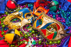 Three Mardi Gras Masks and Beads. Colorful Mardi Gras masks on a background of colored beads and silk
