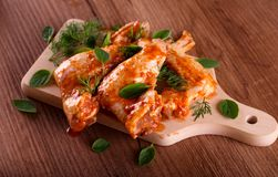Three marinated chicken wings on wooden board Royalty Free Stock Photography