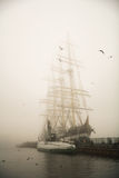 Three-masted Kruzenshtern sailboat. And old diesel submarine S189 in the fog in the port Royalty Free Stock Photo
