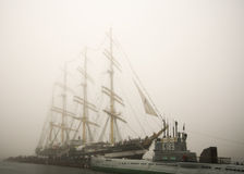 Three-masted Kruzenshtern sailboat. And old diesel submarine S189 in the fog in the port Stock Photos