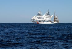 Three masted schooner. A view across the blue water to a three-masted schooner or sailing vessel of the US Coast Guard Royalty Free Stock Photos
