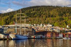 Bergen harbor with schooner, picturesque town and forested hill, Norway. A three-masted schooner with sails furled is docked in the harbor in Bergen, Norway. It Stock Photos