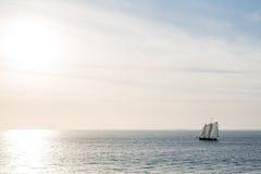Three Masts Sailing Toward Sunset Stock Photography
