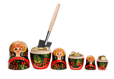 Three Matryoshkas full of coins with shovel Royalty Free Stock Photos