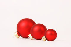 Three matt red christmas balls in a row Stock Photo