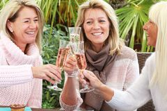 Three mature girlfriends with glasses of sparkling wine Stock Images