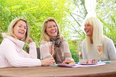 Three mature girlfriends with glasses of sparkling wine Royalty Free Stock Image