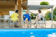 Three mature middle-aged women are having fun and talking, sitting in a lounger by the pool, summer evening.  stock photography