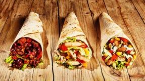 Three meat burritos on table stock image