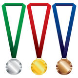 Three medals set. Gold, silver and bronze on red ribbon and green, blue ribbon. Royalty Free Stock Photo