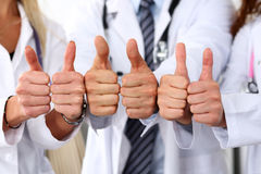 Three medicine doctors show OK sign with thumb up Royalty Free Stock Photo