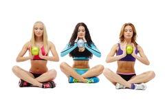 Three meditators girls holding gymnastic balls Stock Photos