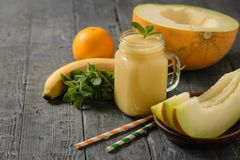 Three melon slices, two cocktail straws and smoothies on a wooden table. stock photography