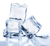 Three melting ice cubes. On glass table. On white background Stock Images