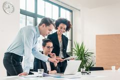 Three members of a young professional team working together. In a modern meeting room Stock Photos