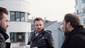 Three men with beards talk. A young red-haired man in the centre, two other stand with their backs to camera. Slow mo. Three handsome men with beards talking stock footage