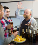 Three men with beer at kitchen Royalty Free Stock Image