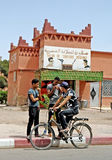 Some Moroccan man parked in front of a coiffeur shop. Three men with bicycle and background an old hairstyle shop for women in ourzazate town in morocco royalty free stock photos