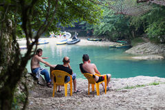 Three men on chairs near the river Stock Photos