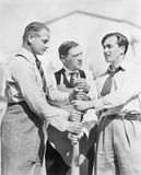 Three men competing who will start first on a baseball bat. (All persons depicted are no longer living and no estate exists. Supplier grants that there will be Stock Photo