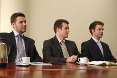 Three Men And A Conference. Three businessmen in suits sitting at a conference table, taking part in a meeting and/or presentation Stock Images