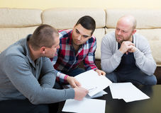 Three men with documents. Discussing financial issues Stock Images