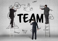 three men drawing a graphic about team on a wall stock photo