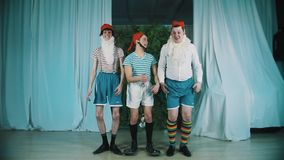 Three men dressed as dwarfes squats few times and fails jump simultaneously. Three caucasian middle aged men dressed as dwarfes in red hats squats few times and stock video