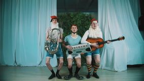 Three men dressed as gnomes with musical instruments jumps and playing music. Three funny caucasian middle aged men dressed as gnomes with musical instruments stock video footage